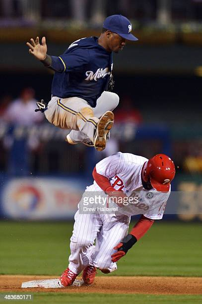 Jean Segura of the Milwaukee Brewers hurdles over Tony Gwynn of the Philadelphia Phillies after putting him out at second base in the sixth inning at...