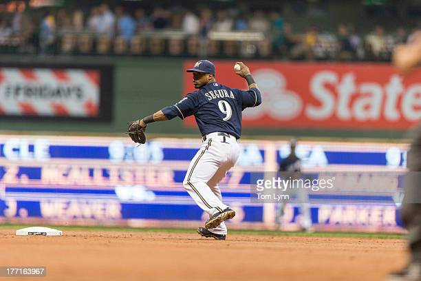 Jean Segura of the Milwaukee Brewers makes a throw to first base against the St Louis Cardinals batter in the first inning at Miller Park on August...