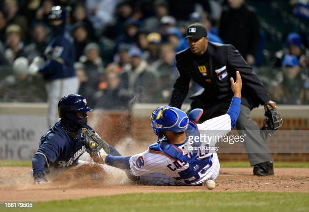Jean Segura of the Milwaukee Brewers scores past catcher Welington Castillo of the Chicago Cubs on a fielder's choice ground ball hit by Norichika...
