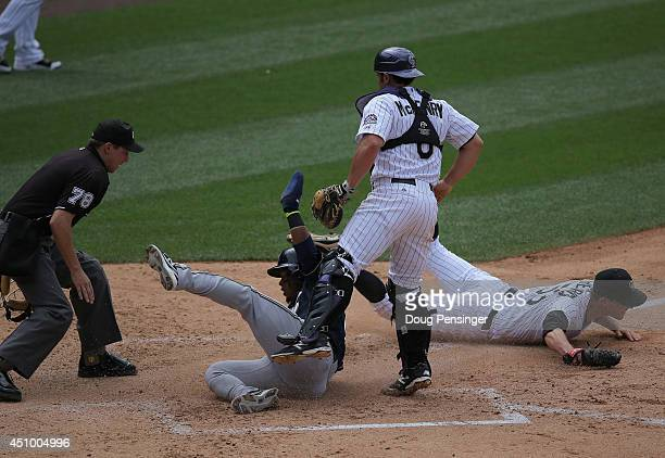 Jean Segura of the Milwaukee Brewers slides home to score as starting pitcher Christian Friedrich of the Colorado Rockies misses the tag and umpire...
