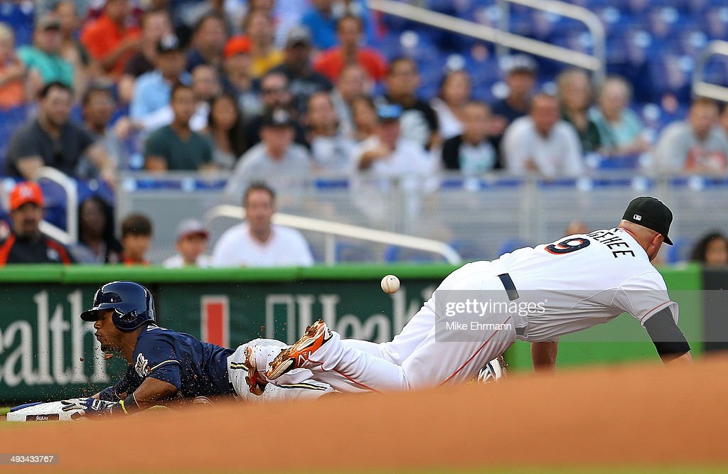 Jean Segura #9 of the Milwaukee Brewers slides into third as Casey McGehee #9 of the Miami Marlins misses the throw during a game at Marlins Park on May 23, 2014 in Miami, Florida.