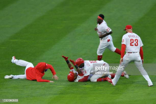 Jean Segura of the Philadelphia Phillies celebrates his game-winning RBI single in the 10th inning with teammates Didi Gregorius, Archie Bradley and...