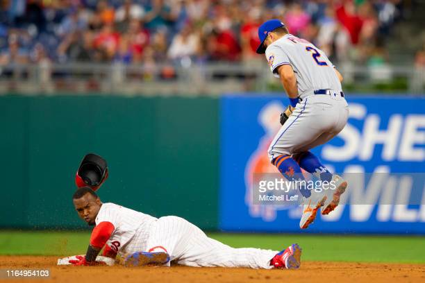 Jean Segura of the Philadelphia Phillies slides in safely past Joe Panik of the New York Mets after hitting a double in the bottom of the sixth...