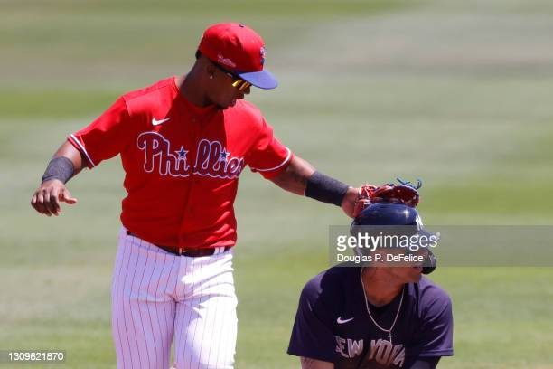 Jean Segura of the Philadelphia Phillies taps Gleyber Torres of the New York Yankees on the helmet after Gleyber Torres was caught stealing during...