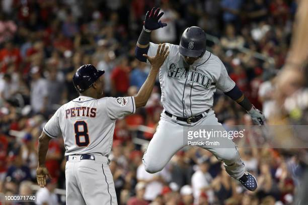 Jean Segura of the Seattle Mariners and the American League celebrates with third base coach Gary Pettis of the Houston Astros after hitting a...