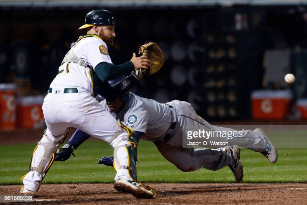 Jean Segura of the Seattle Mariners dives into home plate to score the game winning run ahead of a tag from Jonathan Lucroy of the Oakland Athletics...