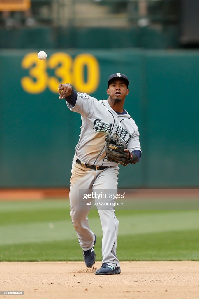 Jean Segura #2 of the Seattle Mariners fields the ball at shortstop and throws to first base to get the out of Khris Davis #2 of the Oakland Athletics in the eighth inning at Oakland Alameda Coliseum on August 9, 2017 in Oakland, California.