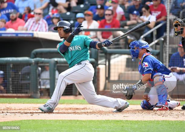 Jean Segura of the Seattle Mariners follows through on an RBI single as catcher Juan Centeno of the Texas Rangers looks on during the second inning...