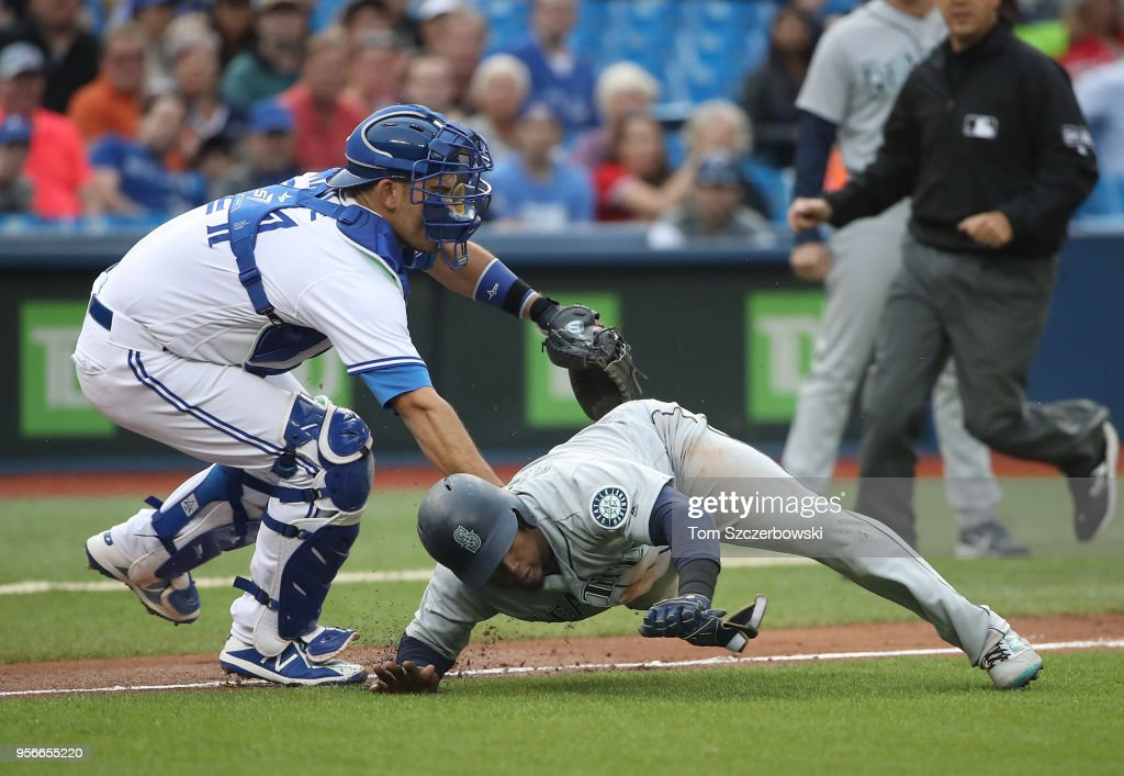 Jean Segura #2 of the Seattle Mariners is tagged out by Luke Maile #21 of the Toronto Blue Jays as he is caught in a run-down during MLB game action at Rogers Centre on May 9, 2018 in Toronto, Canada.