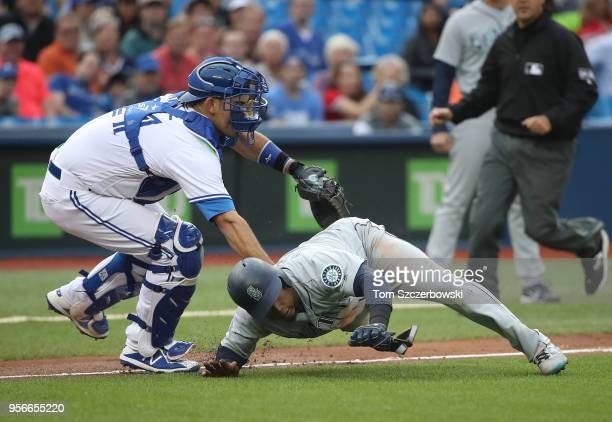 Jean Segura of the Seattle Mariners is tagged out by Luke Maile of the Toronto Blue Jays as he is caught in a rundown during MLB game action at...