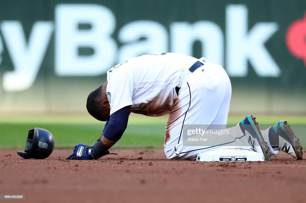 Jean Segura #2 of the Seattle Mariners lays on the ground injured after sliding into second against the Tampa Bay Rays during their game at Safeco Field on June 2, 2018 in Seattle, Washington.
