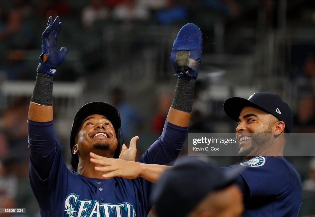 Jean Segura #2 of the Seattle Mariners reacts with Nelson Cruz #23 after scoring on a two-RBI single hit by Taylor Motter #21 in the eighth inning at SunTrust Park on August 23, 2017 in Atlanta, Georgia.