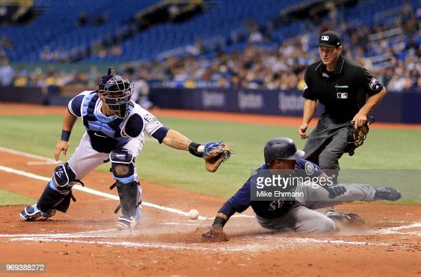 Jean Segura of the Seattle Mariners slides in front of the tag from Wilson Ramos of the Tampa Bay Rays in the second inning during a game at...