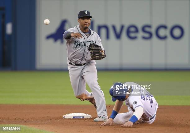 Jean Segura of the Seattle Mariners turns a double play in the eighth inning during MLB game action as Josh Donaldson of the Toronto Blue Jays slides...