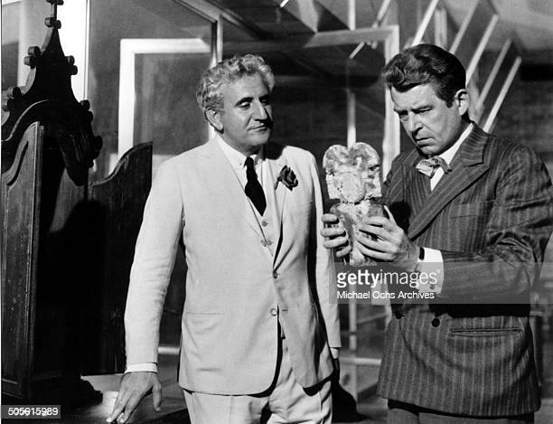 Jean Servais looks on as Adolfo Celi demands to see the statue in a scene from the United Artist movie 'That Man from Rio' circa 1964