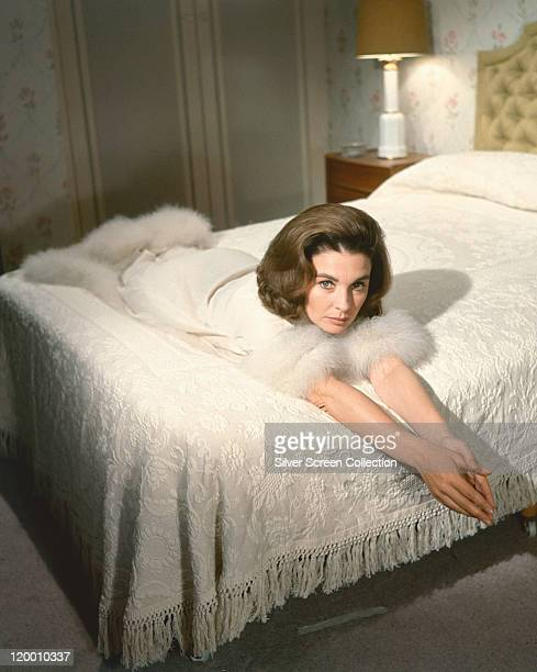 Jean Simmons Britiish actress wearing a white dressing gown with white fur cuffs and hem reclining on a bed with white covers in a studio portrait...