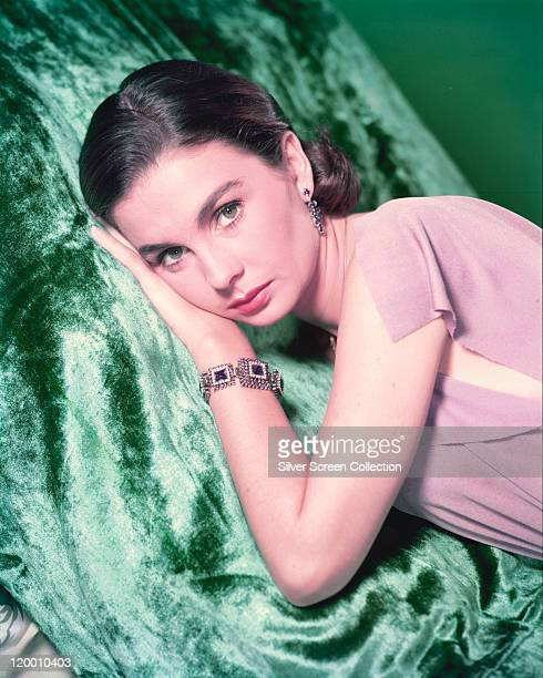 Jean Simmons Britiish actress wearing an ornate bracelet as she lays on a green fabric surface in a studio portrait circa 1955
