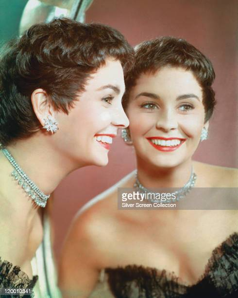Jean Simmons . Britiish actress, wearing diamond earrings and necklace, and a black shoulderless dress, smiling at her reflection in a mirror in a...