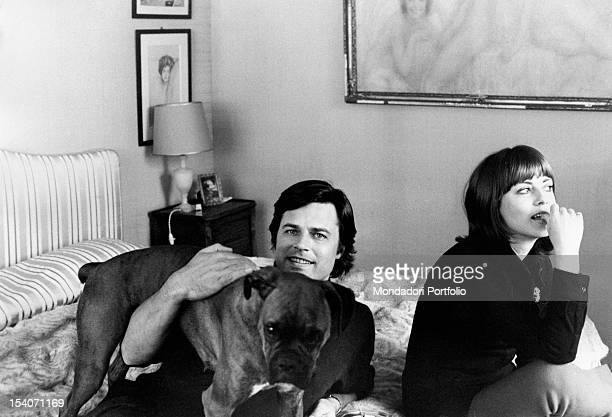 Jean Sorel and his wife Anna Maria Ferrero are in the bedroom seated on the bed with their dog the actor hugs the dog looking to camera while Anna...