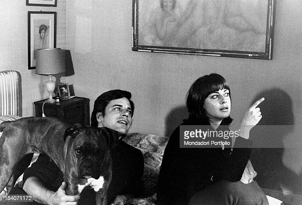 Jean Sorel and his wife Anna Maria Ferrero are in the bedroom seated on the bed with their dog the couple is looking at something with interest...