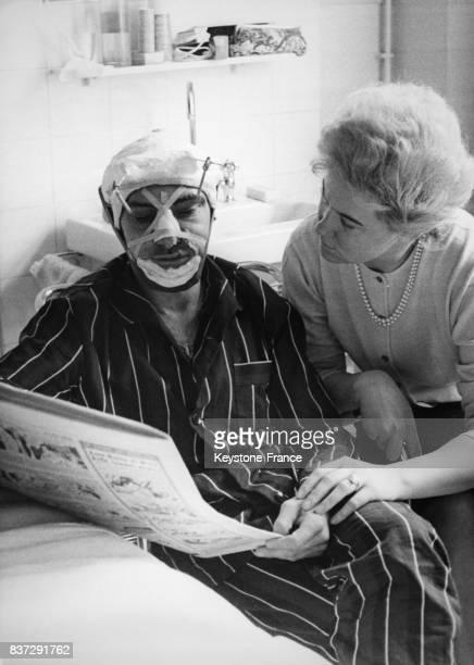 Jean Stablinski à l'hôpital SaintAntoine où il est soigné après une grave chute lit le journal en compagnie de sa femme Génia à Paris France le 5...