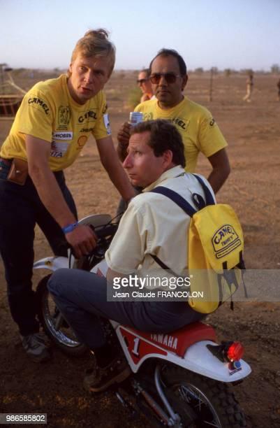 Jean Todt sur une mini moto et le pilote Ari Vatanen en repos lors du rallye ParisDakar le 14 janvier 1987 au Mali