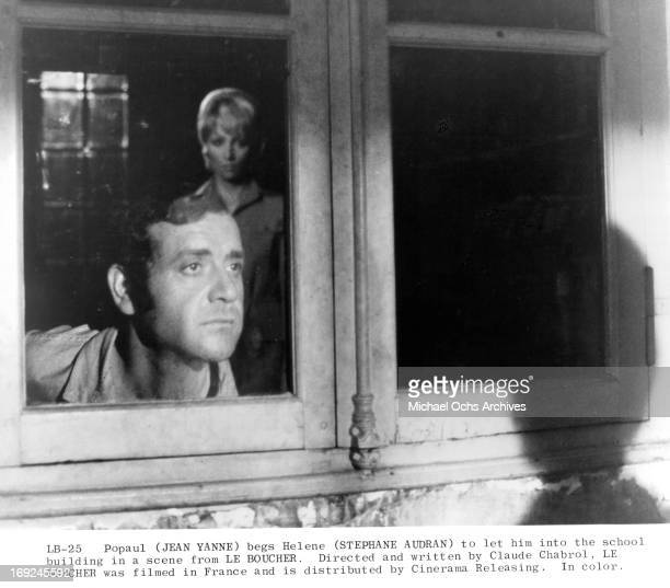 Jean Yanne looks out a window next to Stephane Audran in a scene from the film 'Le Boucher' 1970