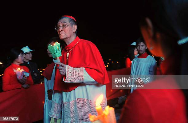 JeanBaptist Cardinal Pham Minh Man Archbishop of Ho Chi Minh City holds a candle while marching in procession as he takes part in the opening...