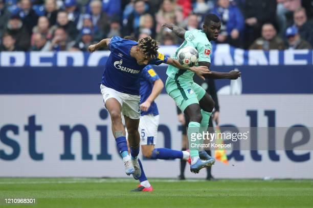 Jean-Clair Todibo of FC Schalke 04 heads the ball under pressure from Diadie Samassekou of TSG 1899 Hoffenheim during the Bundesliga match between FC...