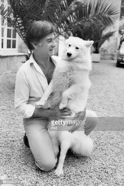 JeanClaude Brialy agenouillé avec un chien dans ses bras en juin 1978 France