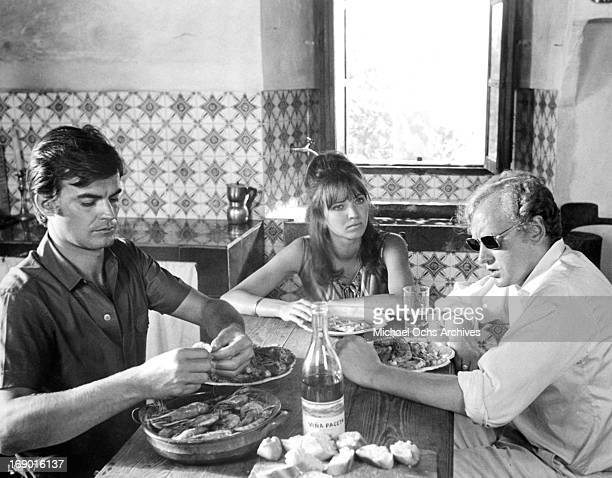 JeanClaude Drouot Anna Karina and Nicol Williamson sitting at a table eating in a scene from the film 'Laughter in the Dark' 1969