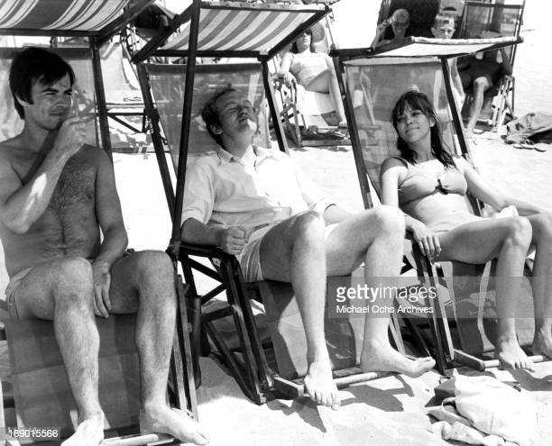 JeanClaude Drouot Anna Karina and Nicol Williamson sitting in lounge chairs as they basque in the sun in a scene from the film 'Laughter in the Dark'...