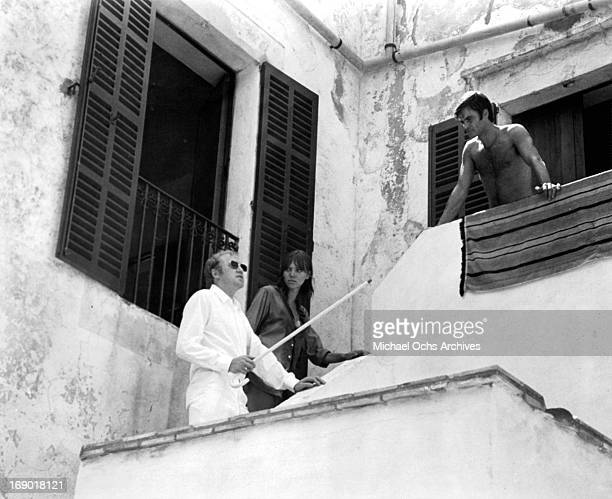 JeanClaude Drouot watches from a balcony as Anna Karina leads Nicol Williamson's up the stairs in the sun in a scene from the film 'Laughter in the...