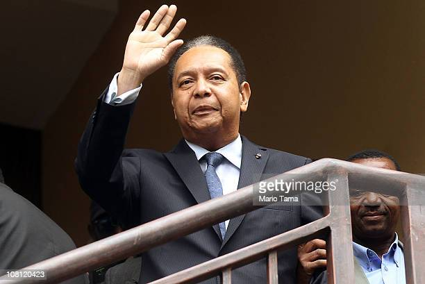 Jean-Claude Duvalier the former Haitian leader known as 'Baby Doc', waves as he is taken into custody by Haitian police at the Hotel Karibe on...