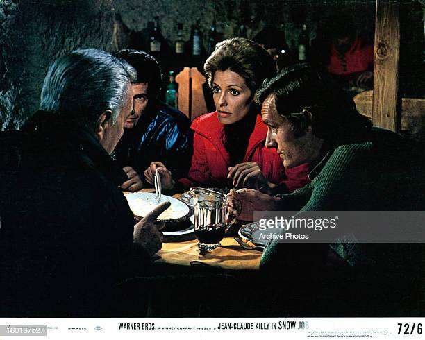 JeanClaude Killy at table with others in a scene from the film 'Snow Job' 1972