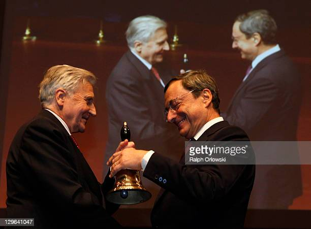 JeanClaude Trichet former president of the European Central Bank hands over a huge bell to his successor Mario Draghi during a farewell celebration...