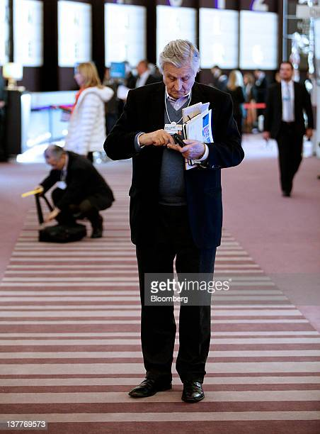 JeanClaude Trichet president of the European Central Bank checks his mobile phone at the Congress Center during day two of the World Economic Forum...