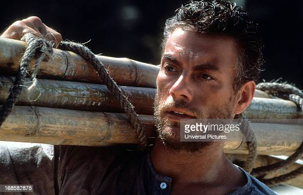 Jean-Claude Van Damme carries bamboo in a scene from the film 'The Quest', 1996.