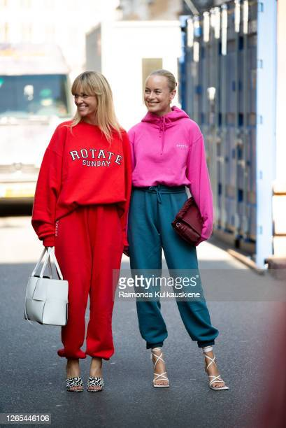Jeanet Madsen wearing red sweatpants, high-heels and a jamper and Thora Valdimars wearing blue sweatpants, high-heels and pink jamper outside...