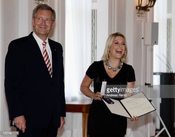 Jeanette Biedermann receives the Federal Cross of Merit from German President Christian Wulff at Bellevue Castle on August 26 2011 in Berlin Germany