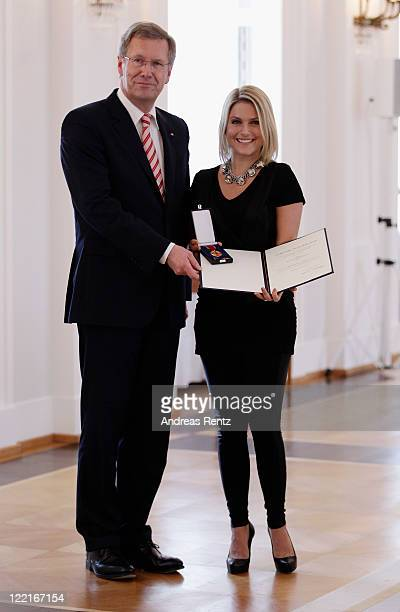 Jeanette Biedermann receives the Federal Cross of Merit from German President Christian Wulff at Bellevue Castle on August 26, 2011 in Berlin,...
