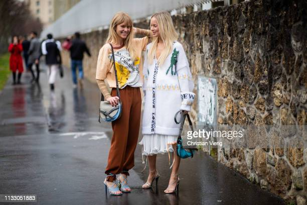 Jeanette Friis Madsen is seen with umbrella wearing heels brown pants bag jumper with print and Thora Valdimars is seen wearing v neck knit dress...