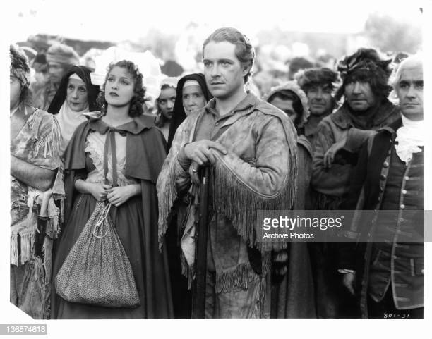 Jeanette MacDonald and Nelson Eddy looking ahead with group of people in a scene from the film 'Naughty Marietta' 1935