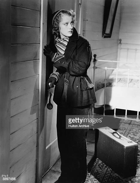 Jeanette MacDonald steals out of a bedroom with a suitcase and a warm winter outfit in a scene from the MGM musical 'Rose Marie' directed by W S Van...