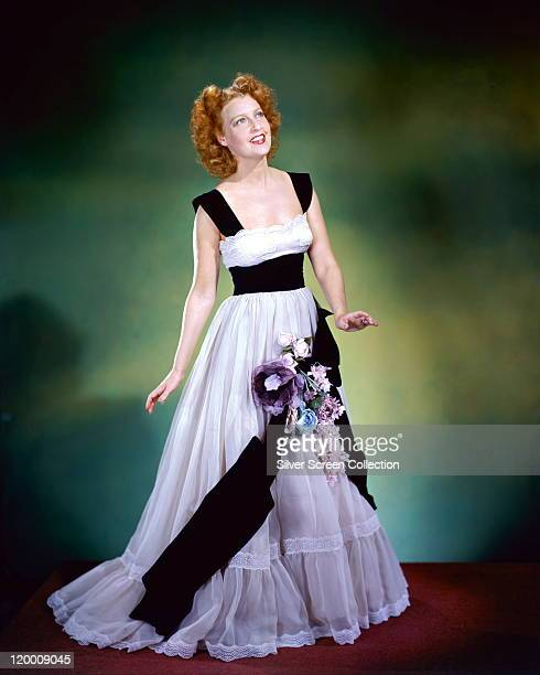 Jeanette MacDonald US actress and singer wearing a long white dress with black trim and decorated with a floral arrangement in a studio portrait...
