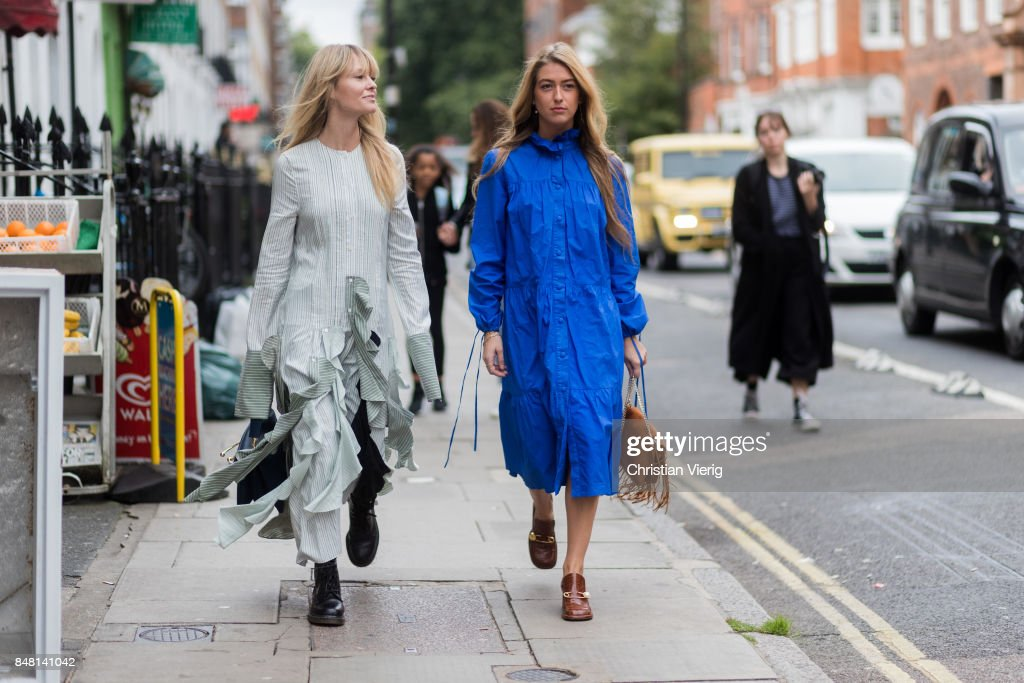 Jeanette Madsen wearing a ruffled dress and Emili Sindlev wearing a brown JW Anderson bag with fringes, blue dress outside JW Anderson during London Fashion Week September 2017 on September 16, 2017 in London, England.