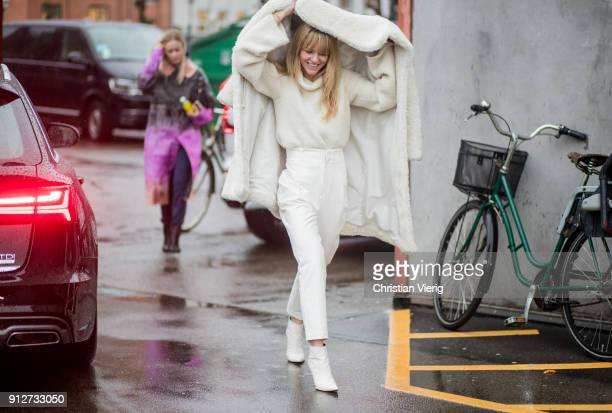 Jeanette Madsen wearing high waisted white pants white teddy coat held over her head turtleneck outside J Lindeberg during the Copenhagen Fashion...