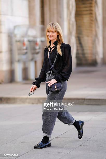 Jeanette Madsen wears a black shirt, a Saint Laurent YSL bag, gray denim large pants, black leather shoes, black socks, outside Vivetta, during Milan...