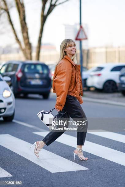 Jeanette Madsen wears a brown leather jacket a Prada white and black bag black leather pants white shoes outside MSGM during Milan Fashion Week...
