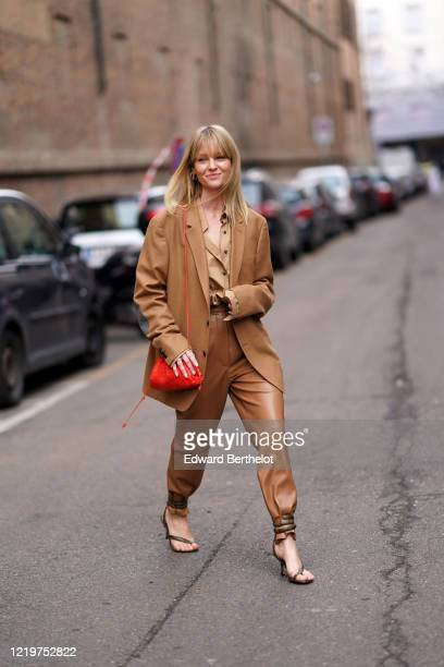 Jeanette Madsen wears a brown oversized blazer jacket a red bag brown leather pants a brown shirt khaki high heel shoes outside Sportmax during Milan...